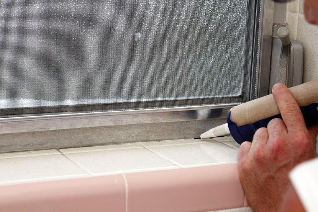 Versiegelungsarbeiten am Fensterrahmen